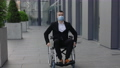 Disabled male ceo executive in 40s wearing medical protective mask and looking ahead while moving at 73805835