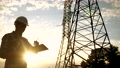 silhouette of an electrician engineer working next to an electrical support tower energy. electricity high voltage tower support. electrical sunset engineer inspect voltage electricity pylon 73810848