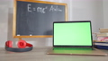 Close-up of laptop with chromakey screen on desk in classroom with headphones and blurred chalkboard at background. Green screen device indoors at school. Modern technologies concept. 73869783