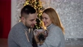 A couple in love with their dog in the living room decorated for Christmas 73880953