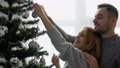 Couple decorating the Christmas tree together in the Christmas Eve 73880955