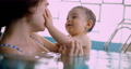 Mother and happy baby touching face smiling in indoor pool 73906187