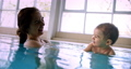 Mother playing with baby in indoor pool 73906195