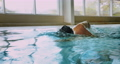 Adaptive amputee professional swimmer front crawl swimming in indoor pool 73906197