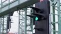 A railway signal light changing from orange to green to control train traffic. Color railroad light signals attached to metal crossing above train tracks in Germany.  4K. 73955951