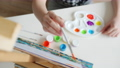 High angle view of child's hand painting picture on easel working with colorful paints at home 73956961