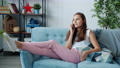 Emotional teenager enjoying conversation on mobile phone relaxing on couch in living room 73956962
