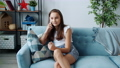 Pretty teen kid speaking on mobile phone smiling sharing news sitting on couch in apartment 73956967