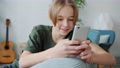 Slow motion of happy teenage boy using smartphone touching screen and smiling at home 73956977