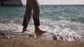 Man walking on the beach. Sea waves touching his feet 74015187
