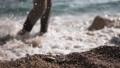 Man walking on the beach. Sea waves touching his feet 74015188