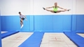 View through yellow safety net of young sporty people exercising jump elements in trampoline center  74059368