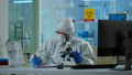 Biologist in ppe suit working on microscope and writing information on clipboard 74130274