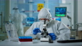 Scientist in ppe suit making adjustments and looking through laboratory microscope 74130276