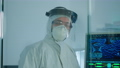 Microbiologist in ppe suit standing in laboratory looking at camera 74130278