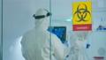Team of chemist doctors wearing protection suit working in danger area 74130281