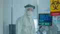 Doctor in ppe suit against covid-19 looking at camera behind the glass wall 74130285