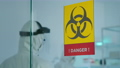 Team of scientists in coverall researching virus mutations working in danger zone 74130286