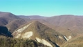 Drone flying above brown mountain forest in sunny day 74201085
