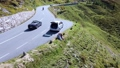 Drone view of sweet couple sitting on mountain hill near the road and drinking 74233234