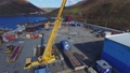 Yellow crane loads truck near huge warehouse on ocean coast 74279527