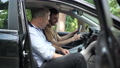 Side view of confident middle aged man teaching young cheerful guy driving. Positive excited Caucasian son or student learning as father or instructor talking. Lifestyle concept. 74317318