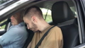 Concentrated young man fastening seat belt with blurred middle aged guy sitting on passenger seat in car. Portrait of confident Caucasian learner studying driving on sunny summer day outdoors. 74317319