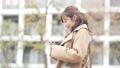 一個女人開始走路看著她的智能手機 74428226