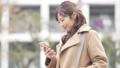 一個女人開始走路看著她的智能手機 74428228