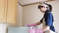 House cleaning woman wiping the top of the fridge with a towel 74428288