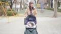 一位三十多歲的母親通過推嬰兒車為一個一歲的孩子走路 74428631
