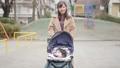 一位三十多歲的母親通過推嬰兒車為一個一歲的孩子走路 74428632