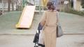 一位三十多歲的母親通過推嬰兒車為一個一歲的孩子走路 74428633