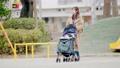 一位三十多歲的母親通過推嬰兒車為一個一歲的孩子走路 74428635