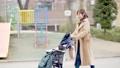 一位三十多歲的母親通過推嬰兒車為一個一歲的孩子走路 74428637