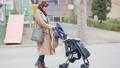 一位三十多歲的母親通過推嬰兒車為一個一歲的孩子走路 74428638
