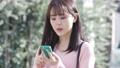 一名年輕女子在行走時停下來,用智能手機確認目的地,然後開始行走 74444850