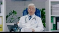 Adult male physician therapist with glasses communicates by video link. Communication with the patient remotely, consultation with a medical specialist. 74489035