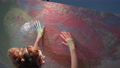 talented female artist with headphones draws with arms on canvas, girl with dirty hands in paint creates colorful and emotional oil painting at workshop, camera in motion 74546827