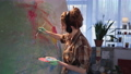 creative artist in headphones uses a brush while creating a painting on large canvas, stylish girl with dirty hands in paint during hobby in studio 74546853