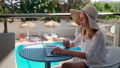 Woman Talks Online using Laptop in Hotel with Swimming Pool on Summer Vacation 74670275