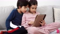Two mixed-race kids sitting on sofa with tablet 74679474