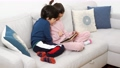 Two mixed-race kids sitting on sofa with tablet 74679476