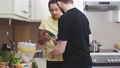 Multinational happy couple cooking vegan food at home 74679477
