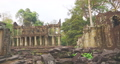 Landscape view of demolished stone architecture and aerial tree root at Preah Khan temple Angkor Wat complex, Siem Reap Cambodia. A popular tourist attraction nestled among rainforest.  74717465