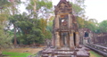 Landscape view of demolished stone architecture and aerial tree root at Preah Khan temple Angkor Wat complex, Siem Reap Cambodia. A popular tourist attraction nestled among rainforest.  74717471