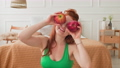 Woman sitting on floor with apples in hands. Female hiding eyes with apples. 74787860