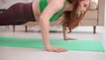Young woman doing push ups exercise at home. Woman fitness training on ground. 74787862