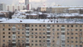 Cleaning the roof from snow in a residential area of Moscow on a sunny winter day after heavy snowfall, Russia  74835631