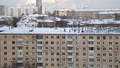 Cleaning the roof from snow in a residential area of Moscow on a sunny winter day after heavy snowfall, Russia  74835632